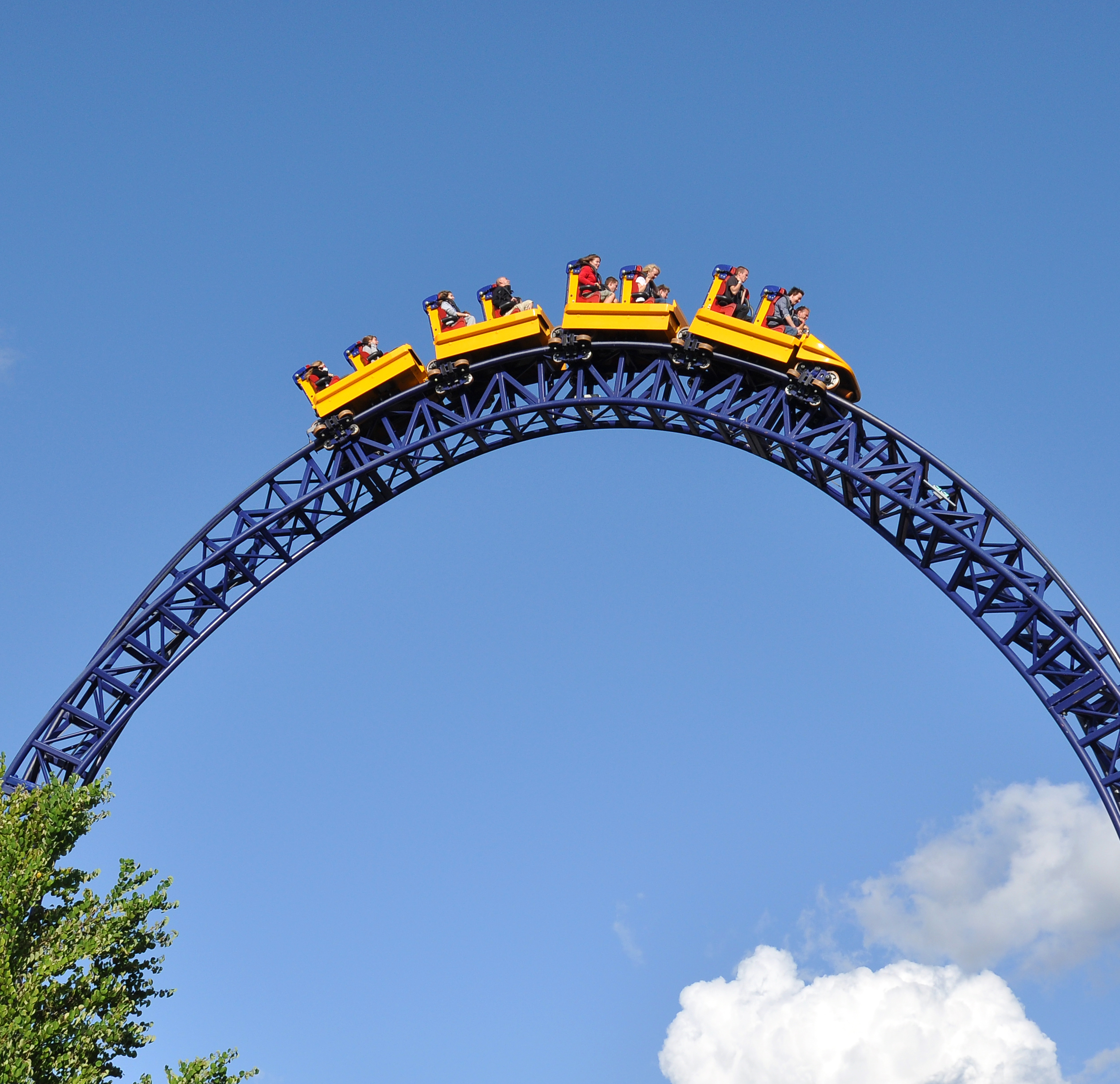Yellow roller coaster on black track against bright blue clear sky